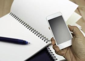 Hand hält Telefon in der Nähe von Notebook foto