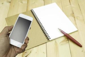 Person, die Telefon mit Notizbuch hält foto