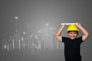 Junge, der einen gelben Ingenieurhut und Hausplanideen auf einer Tafel trägt foto