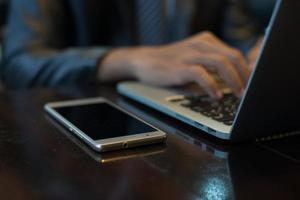 Hände des Geschäftsmannes, die auf einer Laptoptastatur am Arbeitsplatz tippen