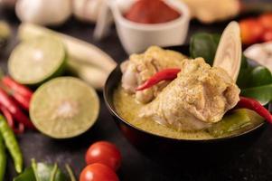 grünes Currygericht mit Huhn, Chili und Basilikum sowie Tomate und Limette