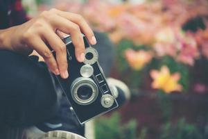 Nahaufnahme der Hand einer Frau mit einer Vintage-Kamera, die Blumen in einem Garten schießt