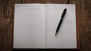 Bild eines offenen leeren Notizbuchs auf Holztisch foto