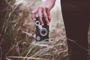 Nahaufnahme der Hand einer jungen Frau, die eine Retro-Kamera in einem Feld hält