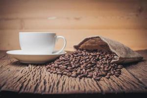 Kaffeetasse mit Kaffeebohnen auf einem Holztisch foto