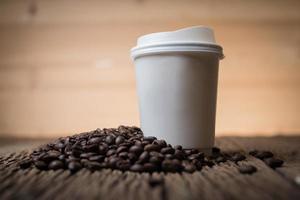 Papierkaffeetasse mit Kaffeebohnen auf einem Holztisch