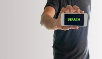 Mann zeigt Telefon mit Suche auf dem Bildschirm foto