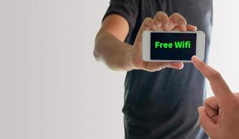 Mann zeigt Telefon mit kostenlosem WLAN auf dem Bildschirm