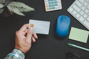 Draufsicht von jemandem, der eine Kreditkarte auf einem Schreibtisch hält