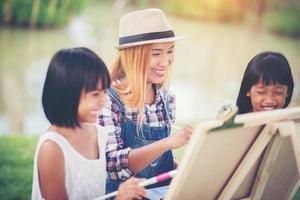 Mutter und Töchter malen gemeinsam Bilder in einem Park foto
