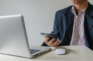 Mann hält Smartphone mit einem Laptop foto