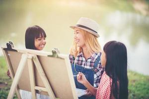Mutter und Töchter malen gemeinsam Bilder in einem Park