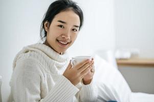 junge Frau, die eine Kaffeetasse im Bett hält foto