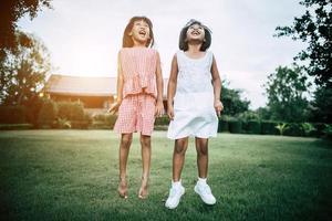 zwei kleine Mädchen, die Spaß haben, im Park zu spielen