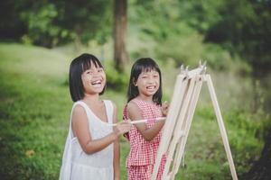 zwei kleine Mädchenmaler, die Kunst im Park zeichnen foto