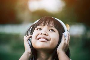 kleines Mädchen, das Musik im Park mit Kopfhörern hört