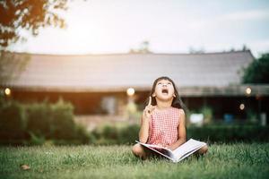 kleines Mädchen liest ein Buch in ihrem Hausgarten draußen