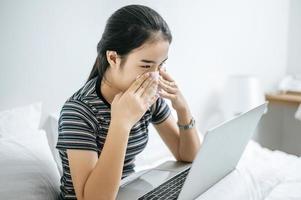 Frau spielt auf Laptop hält ein Taschentuch, um Nase zu wischen foto