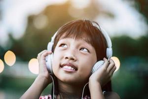 kleines Mädchen, das Musik im Park mit Kopfhörern hört foto