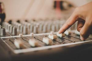 Hände des Toningenieurs, der das Audiomischpult einstellt