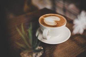 Vintage Ton Tasse heißen Kaffees mit Kunst in einer Herzform foto
