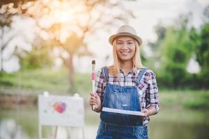 schönes Mädchen, das ein Bild im Park zeichnet foto