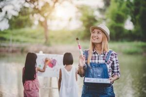 Mutter und Tochter zeichnen Bild zusammen im Park foto