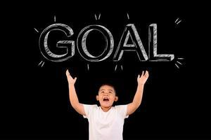 Der Junge breitet die Hände aus, um das Ziel zu zeigen foto
