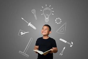 ein Junge und ein Buch des Wissens auf einem Tafelhintergrund foto