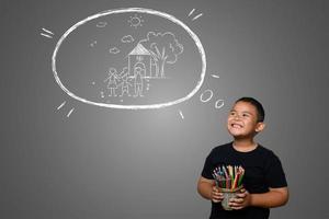 ein Junge mit Stiften, die einen Traumhintergrund zeichnen foto