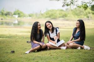 junge Studentinnen bereiten sich auf eine Prüfung im Park vor foto