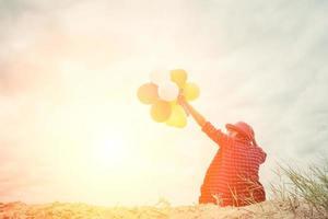 junge Hipsterfrau, die Luftballons unter dem Himmel hält foto