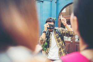 junger Mann, der Bilder seiner Freunde macht, während er zusammen im Stadtgebiet reist foto