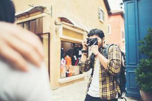 junger Mann, der Bilder seiner Freunde macht, während er zusammen im Stadtgebiet reist