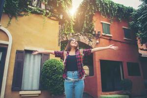 glückliche junge Frau, die ihre Reisen genießt und ihre Hände in die Luft hebt