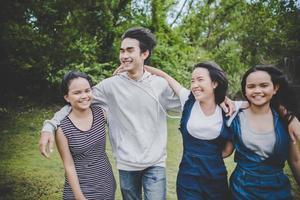 glückliche jugendliche Freunde, die draußen in einem Park lächeln
