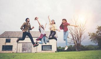glückliche Gruppe von jugendlichen Studenten, die zusammen in einen Park springen foto