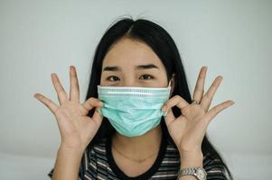 Mädchen trägt eine Hygienemaske, ein gestreiftes Hemd und ein Handsymbol in Ordnung foto