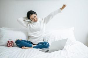 junge Frau, die auf Bett mit Laptop streckt