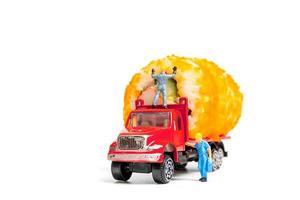 Miniaturleute, die eine Sushi-Rolle auf einem LKW ziehen foto