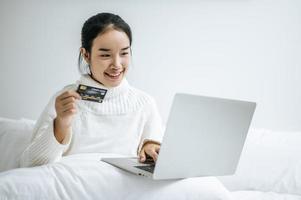junge Frau, die auf Laptop einkauft und eine Kreditkarte hält foto