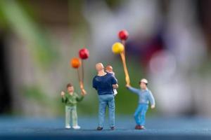 glückliche Miniaturfigurenfamilie, die Luftballons hält