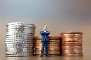 Miniatur-Kleinunternehmer, die mit einem Stapel Münzen stehen