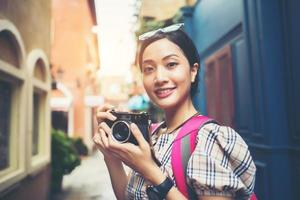 Nahaufnahme einer jungen Hipster-Frau, die Rucksacktouren macht und Fotos in einem städtischen Gebiet macht