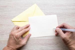 männliche Hände, die auf eine leere weiße Karte schreiben foto