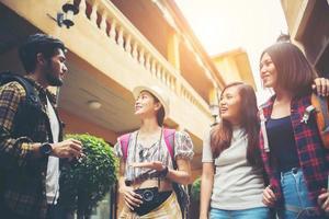 Gruppe von glücklichen jungen Freunden, die Spaß haben, in der städtischen Straße zu gehen