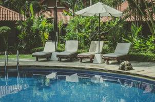 Stühle in der Nähe eines Schwimmbades foto