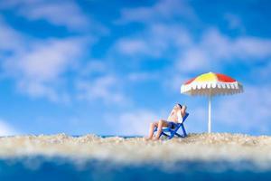 Mann sitzt am Strand mit einem Regenschirm foto