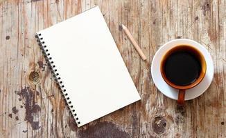 braune Kaffeetasse und Notizbuch foto