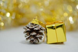 goldene Geschenkbox und Tannenzapfen